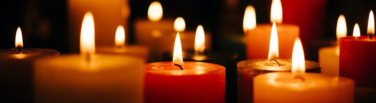 Viele gelb-rötliche Kerzen stehen neben- und hintereinander und brennen; der Hintergrund ist dunkel