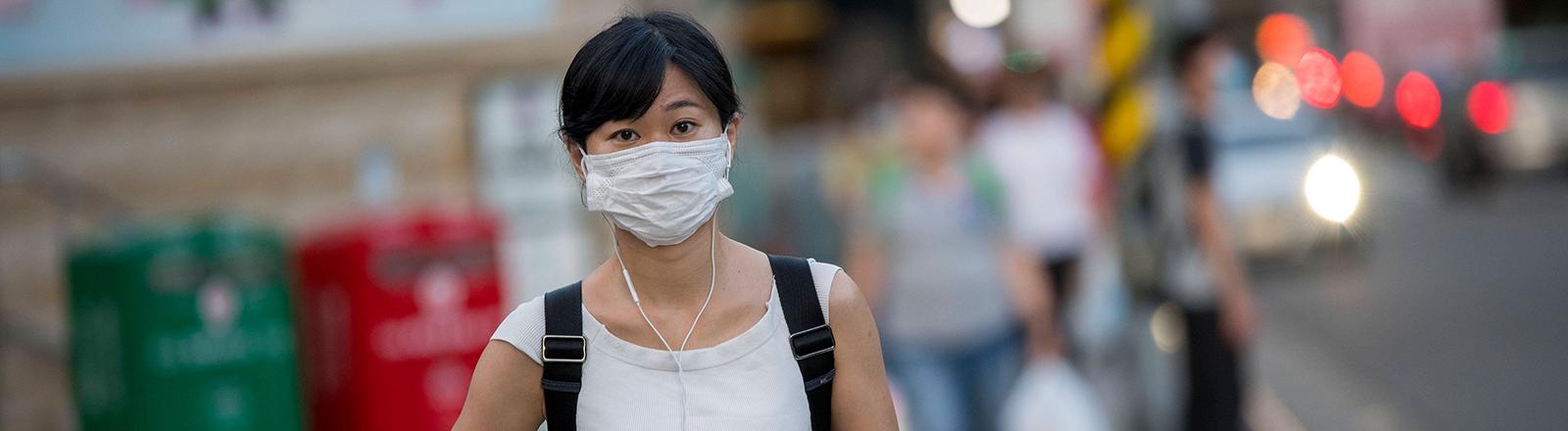 In Taipei, Taiwans Hauptstadt, läuft eine Frau über einen Zebrastreifen; sie trägt Mund-Nase-Schutz (05.08.2020)