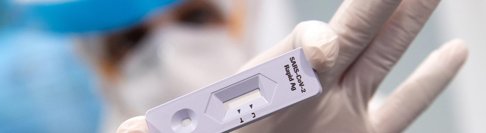 Eine Person in Schutzkleidung hält einen Antigen-Schnelltest in die Kamera; Foto: dpa (12.11.2020)