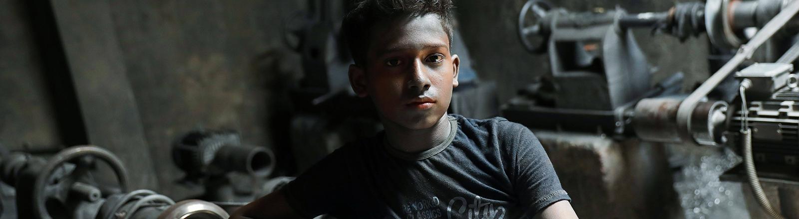 Ein Junge sitzt in einem dunklen Raum mit Werkzeugen und Maschinen; er blickt direkt in die Kamera; der 12-Jährige Hasibur Rahman lebt in Bangladesch und muss arbeiten (30.05.2020)