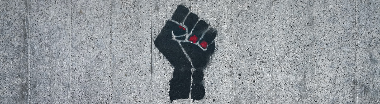 Graffiti einer schwarzen Faust, jemand hat die Nägel rot lackiert.