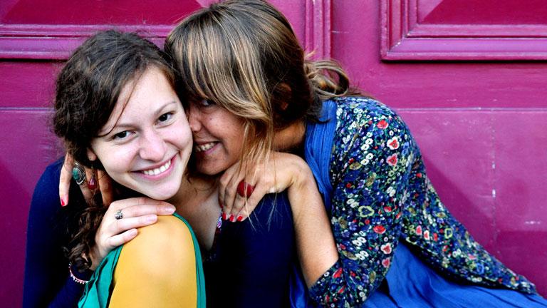 Zwei Freundinnen stecken die Köpfe zusammen und lachen