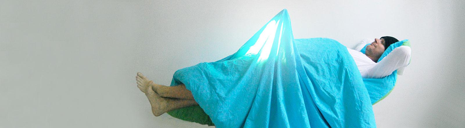 Ein Mann liegt uner einer Decke, auf Höhe seines Penis hat sich eine Beule gebildet