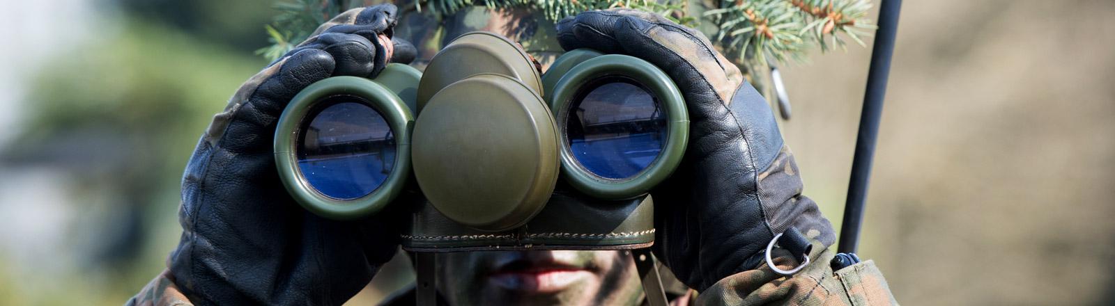 Ein Soldat guckt durch ein Fernglas