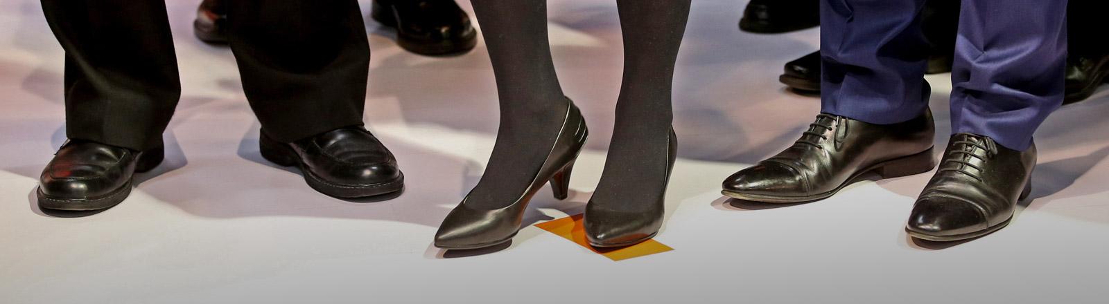 Füße einer Frau zwischen Männern
