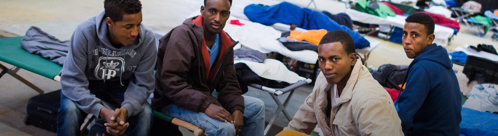 Vier Männer in einer Flüchtlingsunterkunft