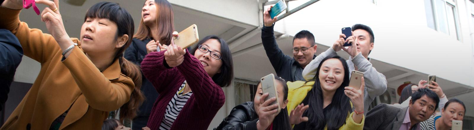Mehrere Menschen fotografieren mit ihrem Smartphone