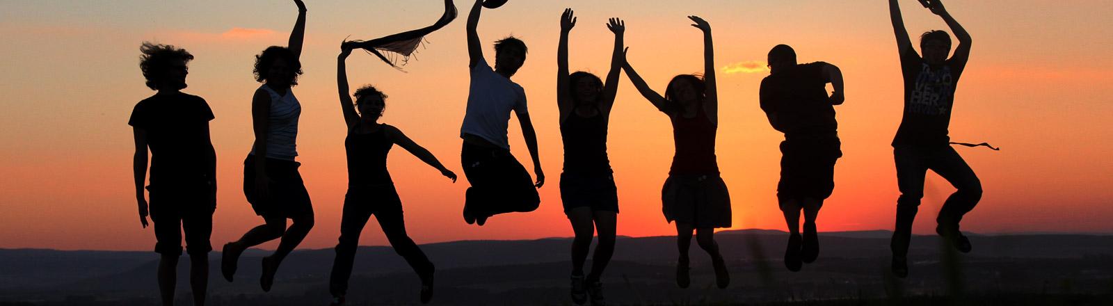 Tanzende Menschen vor einem Sonnenuntergang