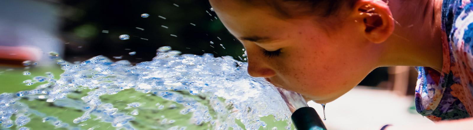 Ein Mädchen trinkt aus einem Gartenschlauch Wasser