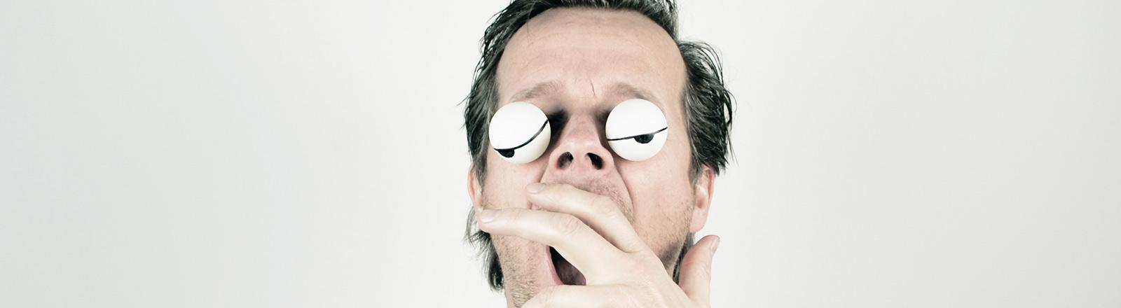 Ein Mann mit weißem Hand gähnt. Er hält sich die Hand vor den Mund. Vor seinen Augen hat er Tischtennisbälle, auf die jeweils ein Auge gezeichnet ist.