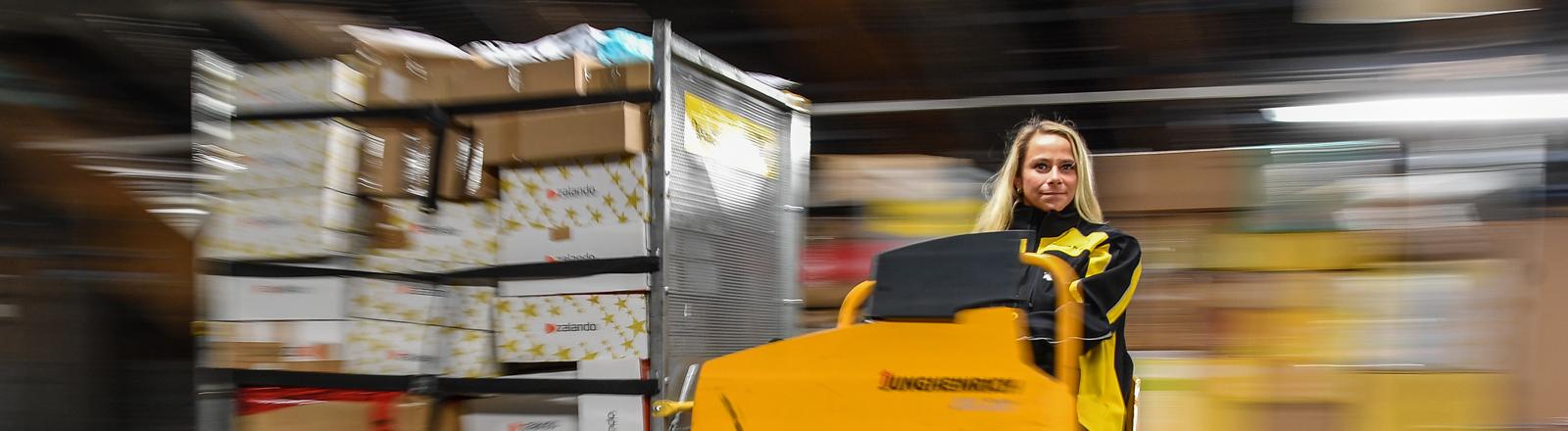 Frau auf einem Transportgerät im Paketzentrum.