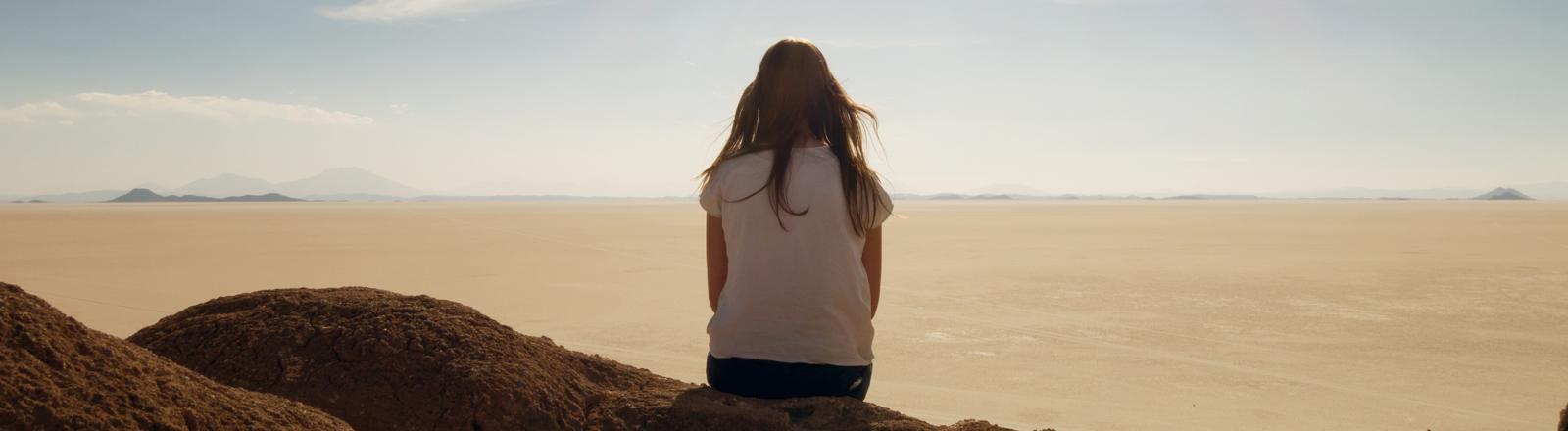 Frau sitzt auf Steinen am Meer