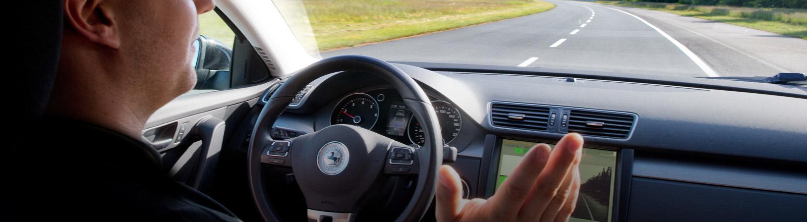 Ein Mann fährt in einem Auto mit Autopilot, die Hände hat er nicht am Lenkrad.