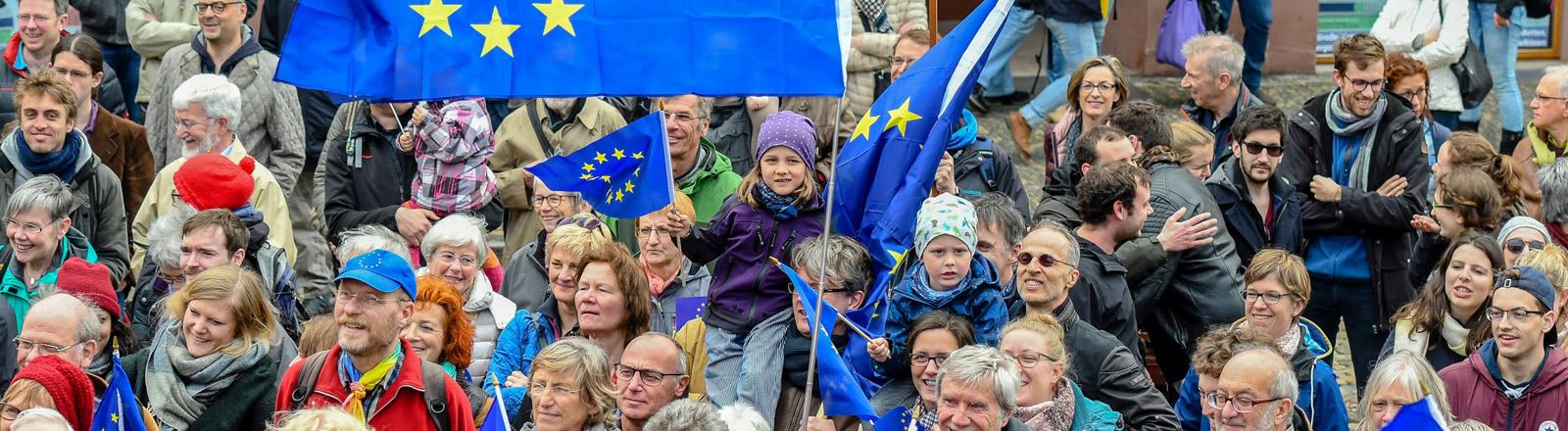 Menschen halten Europaflaggen hoch