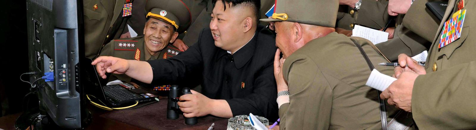 Kim Jong-un sitzt an einem Schreibtisch, begleitet von diversen Männern in Uniform