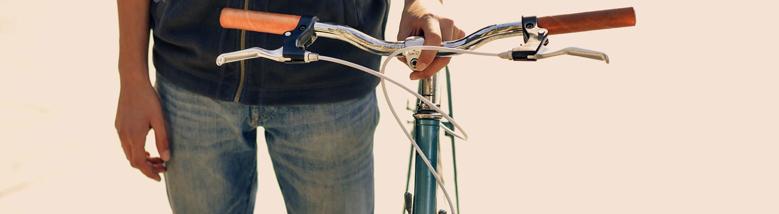 Eine Person hält ein Fahrrad am Lenker