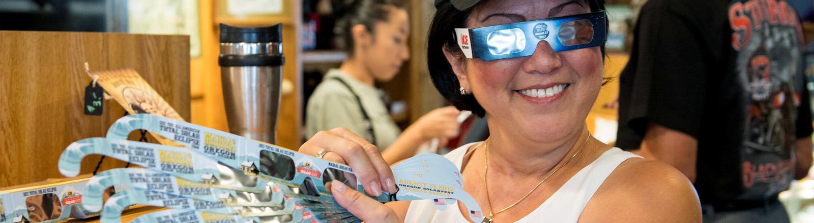 Eine US-Amerikanerin hält sieben spezielle Brillen in der Hand, mit denen sich eine Sonnenfinsternis beobachten lässt.