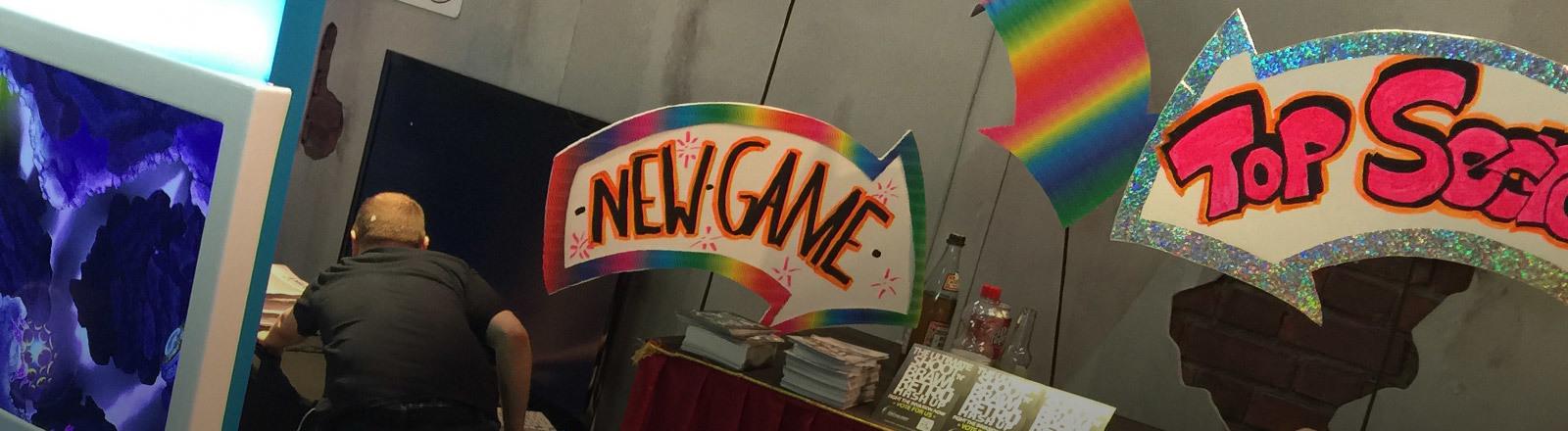 """Ein Computerspiel wird mit den selbstgemalten Schildern """"New Game"""" und """"Top Secret"""" beworben."""