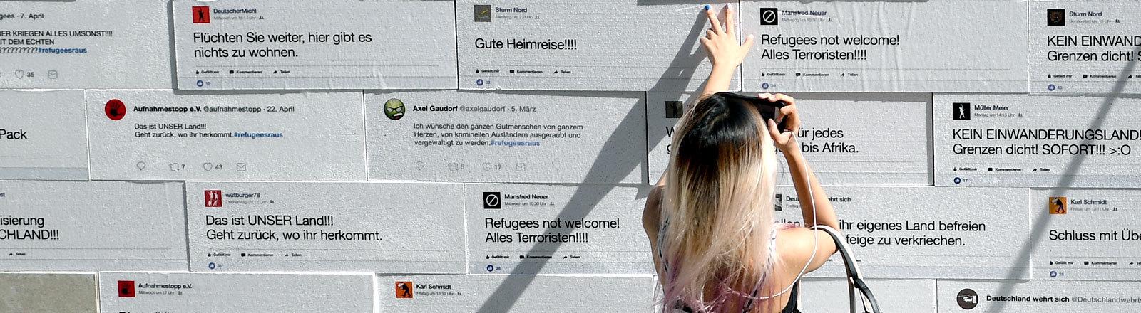 Eine Frau an einer Wand, an der Papptafeln mit aufgedruckter Hate Speech befestigt sind.