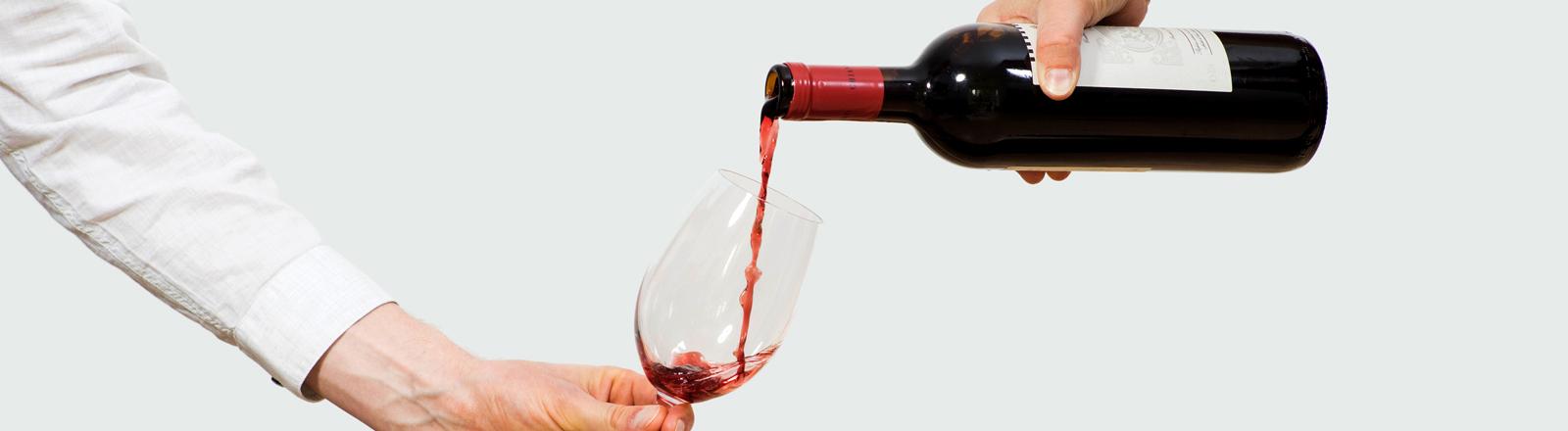 Wein wird in ein Glas geschüttet