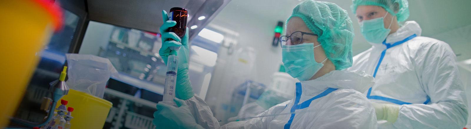 Zwei Mitarbeiter stellen in einem Reinraum Krebsmedikamente her.