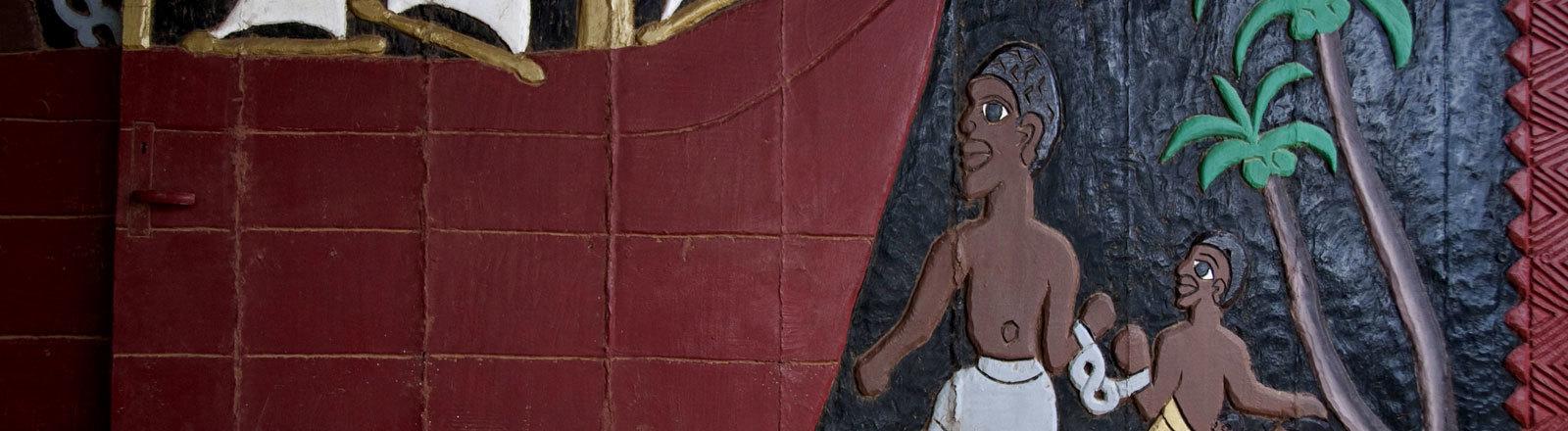 Eine alte Holzschnitzerei, die Sklaven zeigt