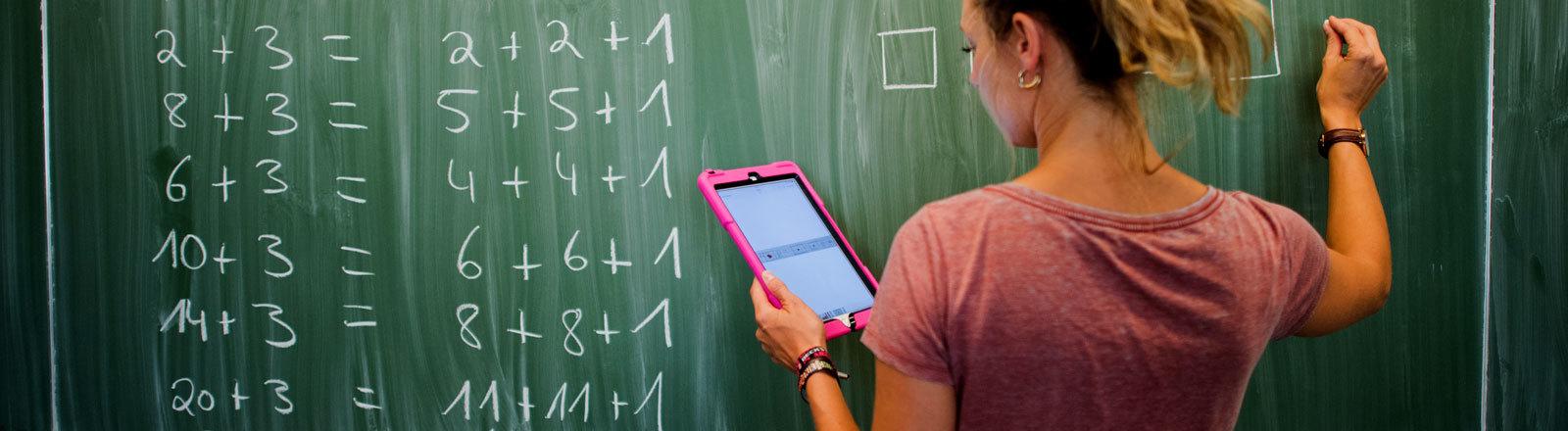 Lehrerin mit Tablet an der Tafel
