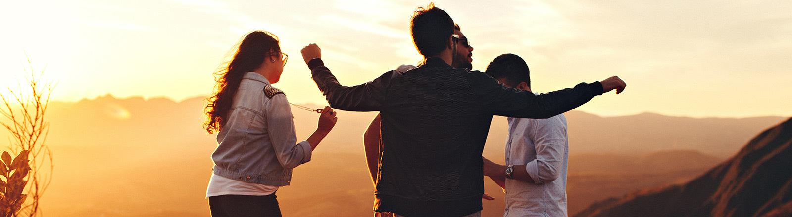 Vier Leute stehen beisammen in der Natur