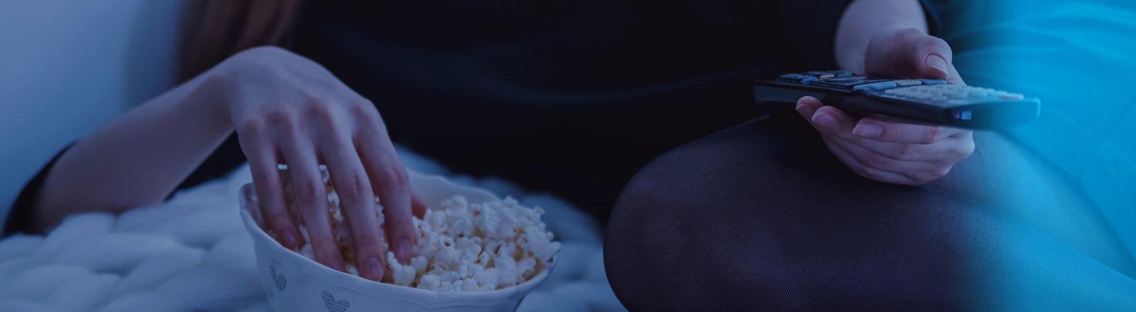 Eine Frau mit Fernbedienung in der Hand isst Popcorn