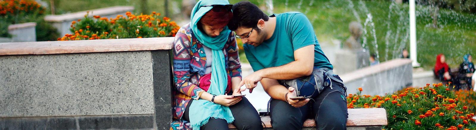 Zwei Menschen mit  Smartphone in Iran