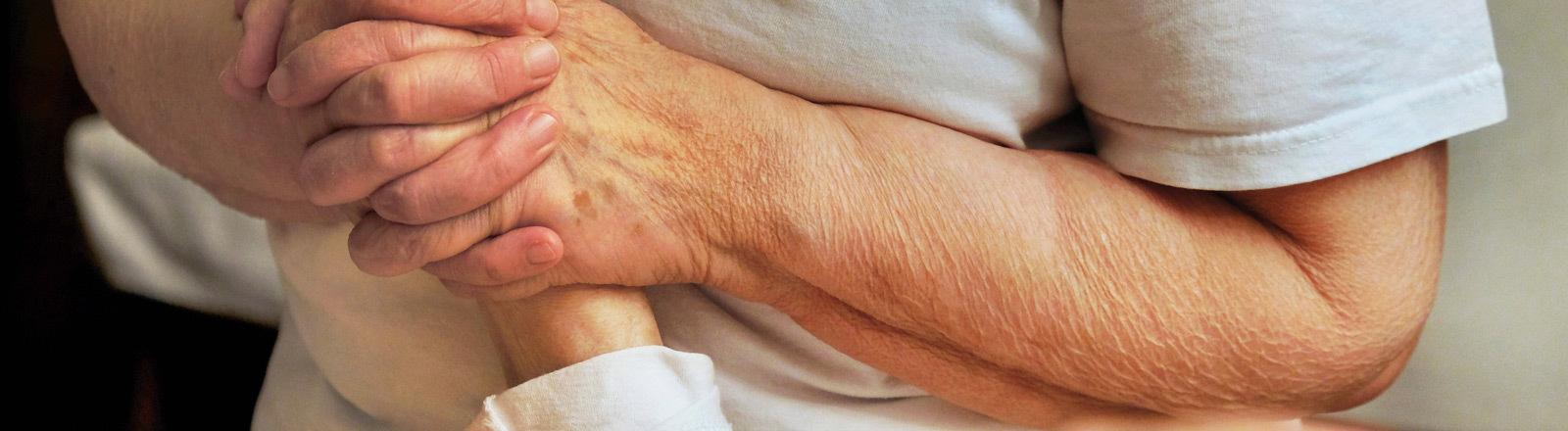 Eine Frau hält die Hand eines Mannes