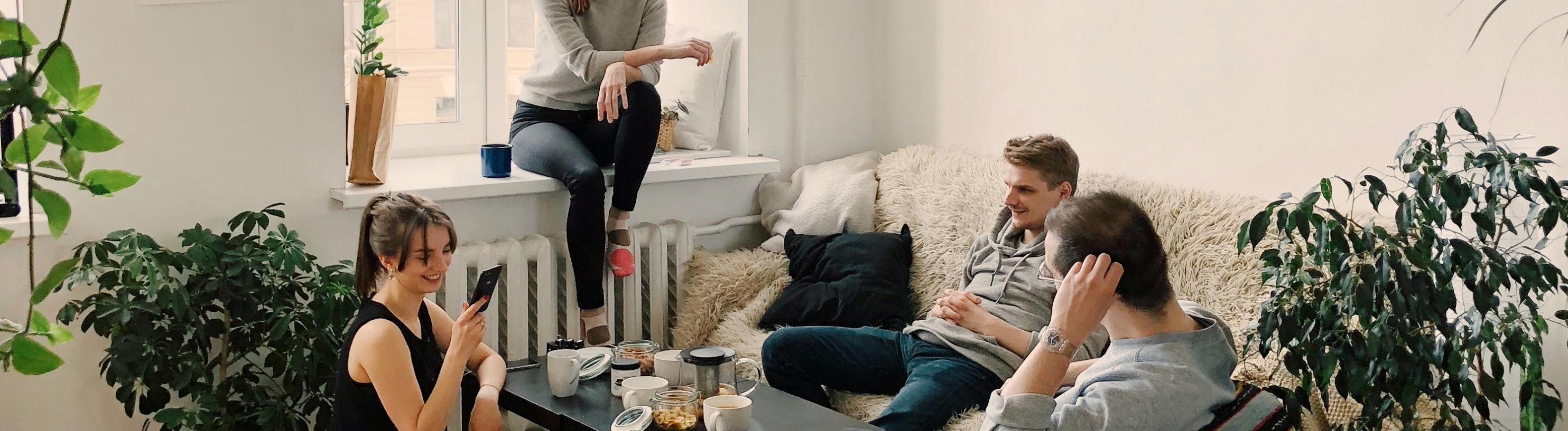 Vier Menschen sitzen um einen Wohnzimmertisch.