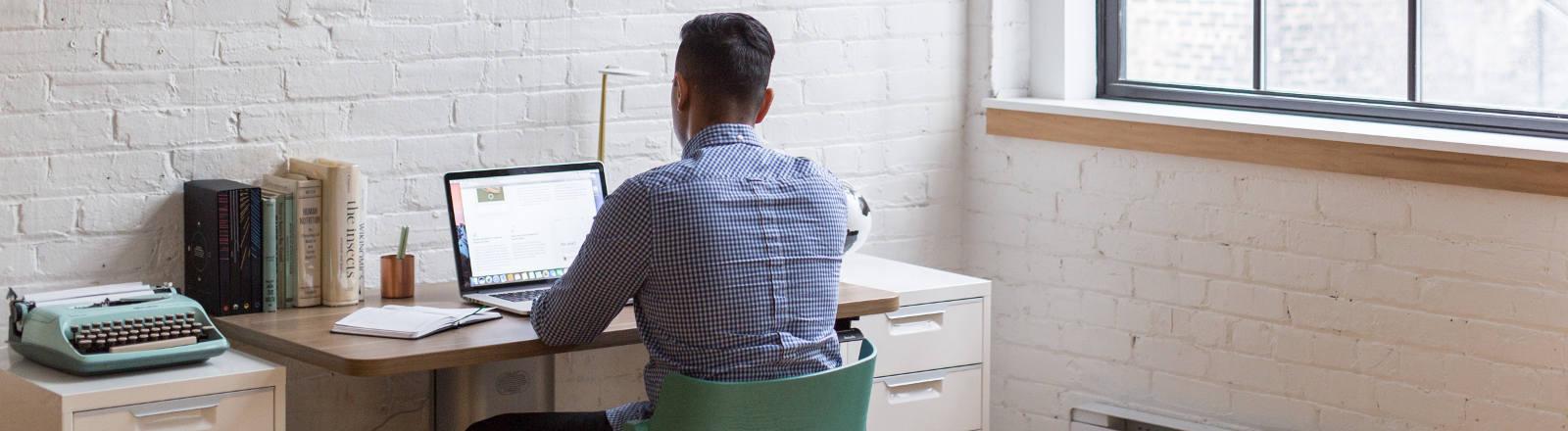Ein Mann sitzt an einem Schreibtisch vor einem Notebook