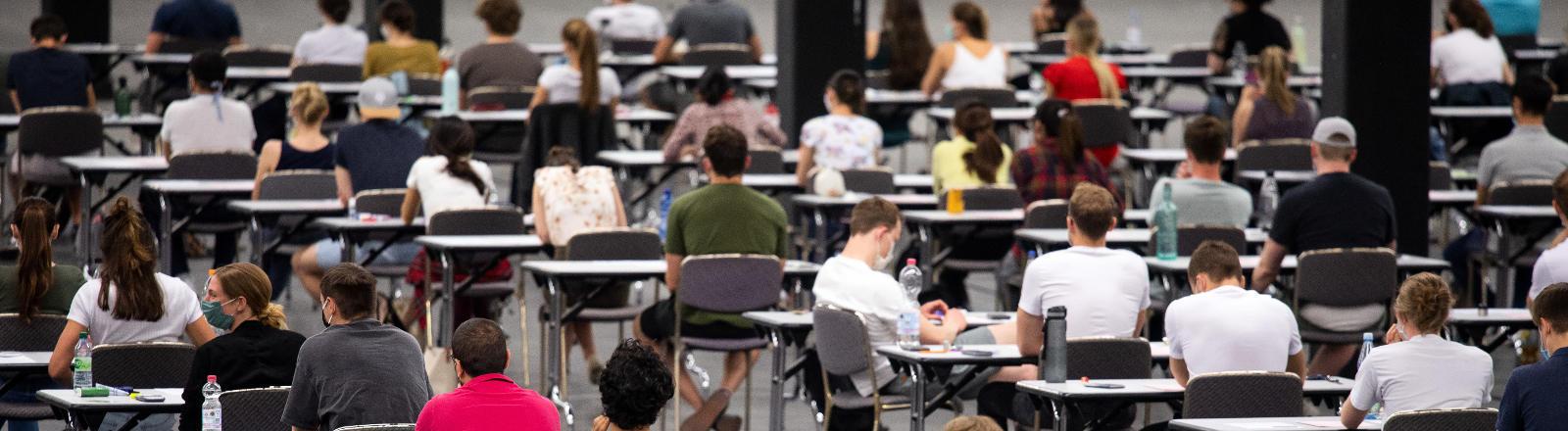 Studierende nehmen in einer Messehalle an einer Prüfung teil