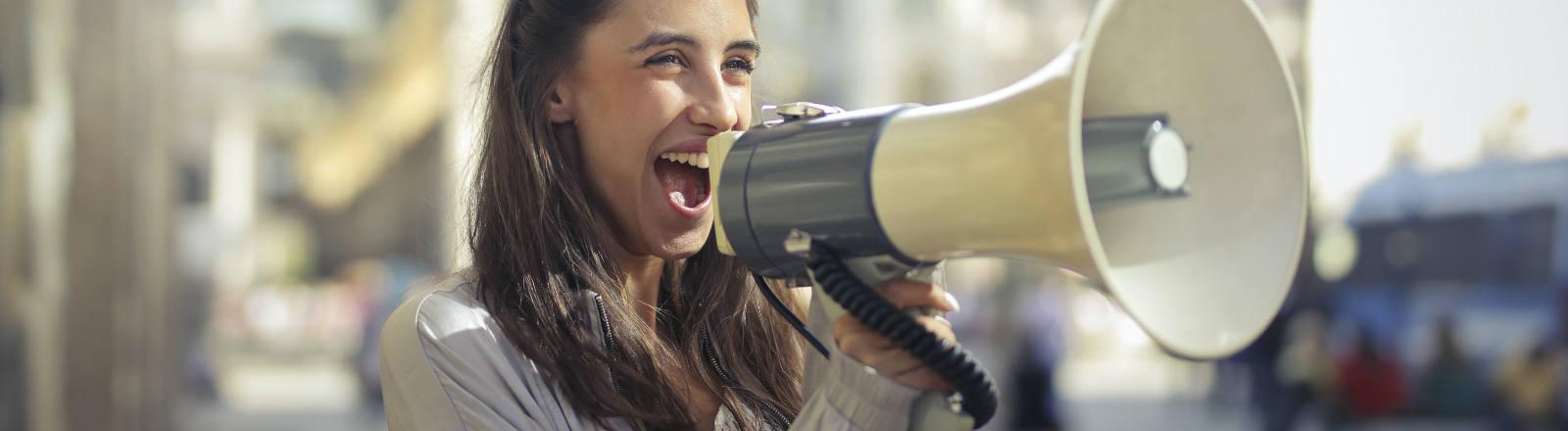 Eine Frau hält ein Megaphone in der Hand
