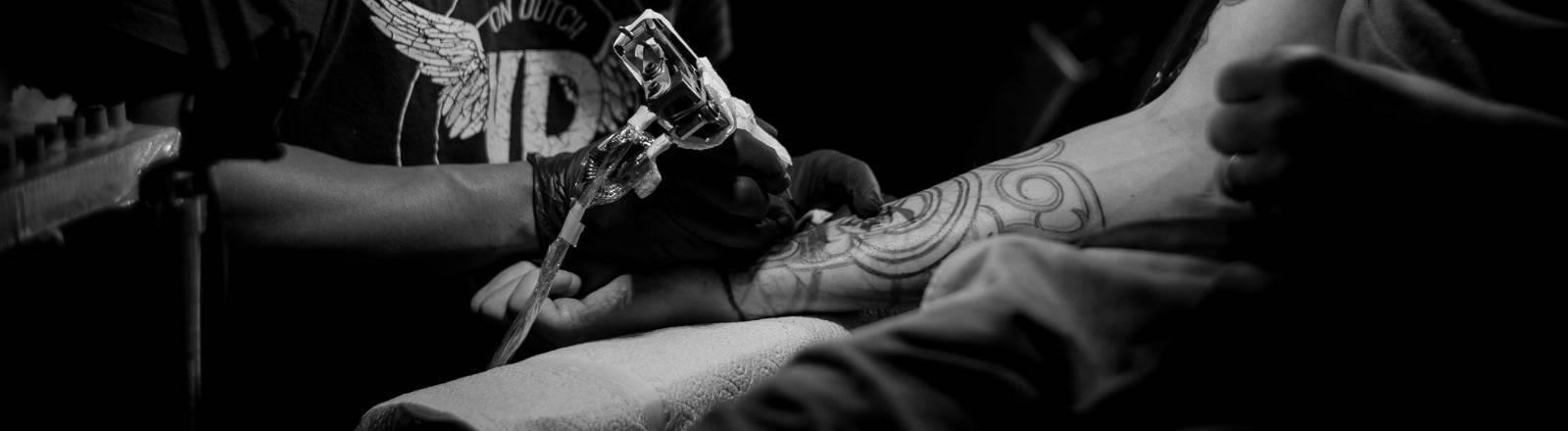Ein Tätowierer sticht ein Tattoo