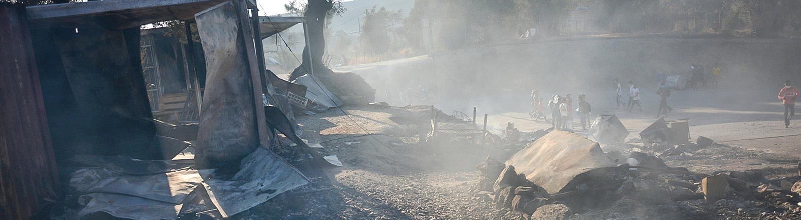 Szene im Flüchtlingslager Moria nach einem Brand. Es liegen verkohlte Gegenstände herum, ein Container ist komplett ausgebrannt, es raucht und Menschen gehen umher (09.09.2020)