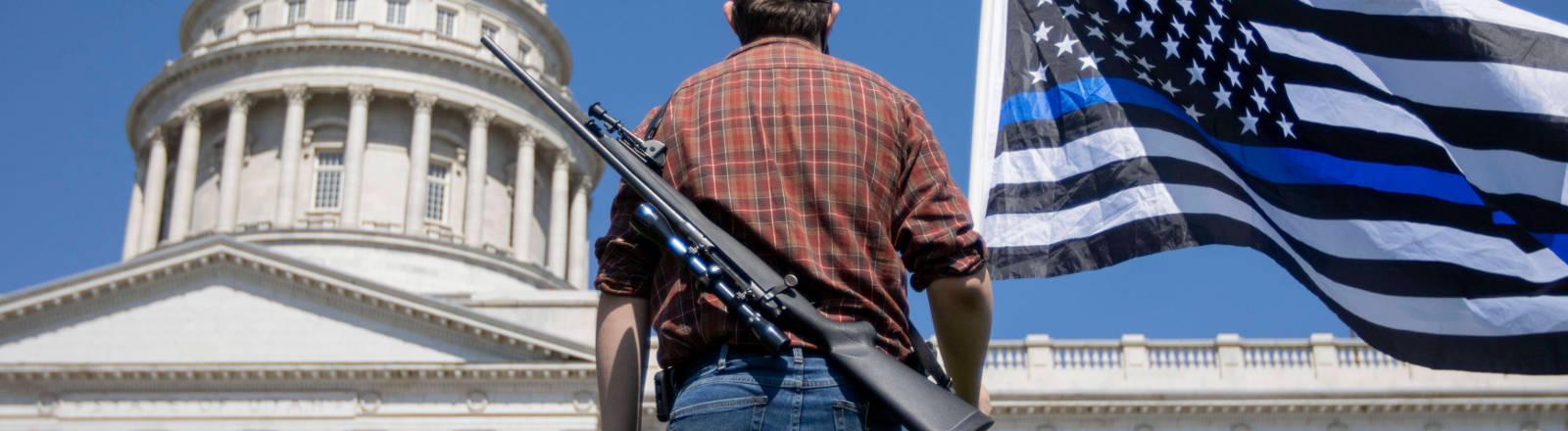 Ein Mann mit einem Gewehr auf dem Rücken vor dem Weißen Haus