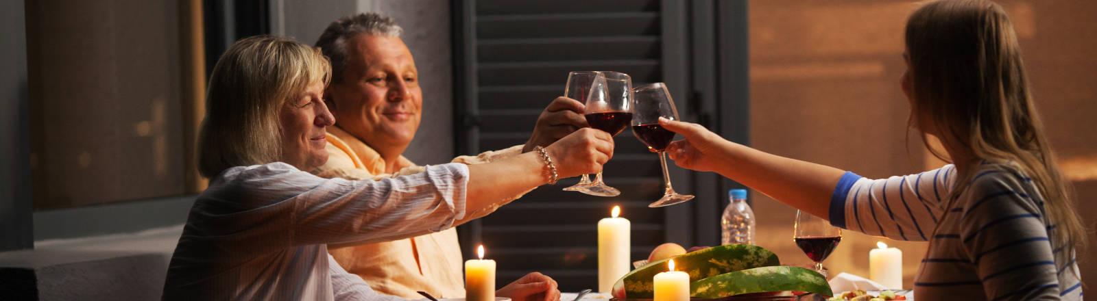 Eine Familie am Tisch mit einem Glas Wein in der Hand