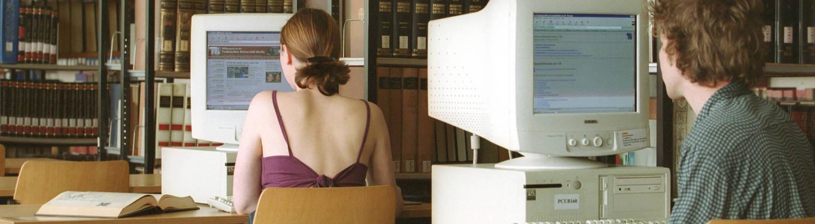 Zwei Studierende an PCs einer Hochschul-Bibliothek