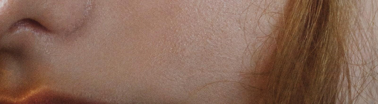 Das Gesicht einer Frau in Nahaufnahme. Ihre Poren sind zu sehen.