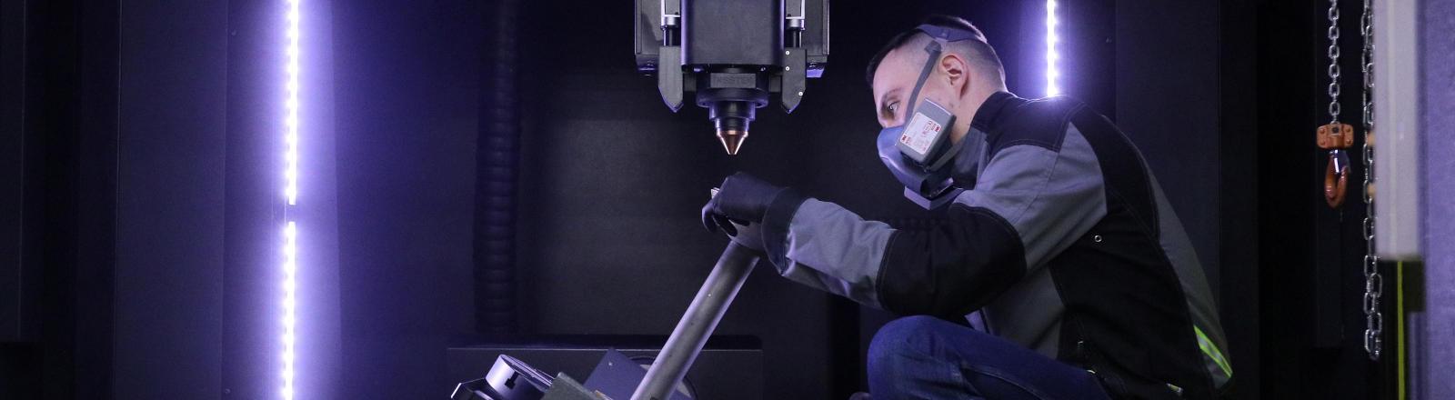 Ein Arbeiter an einem Industrieroboter