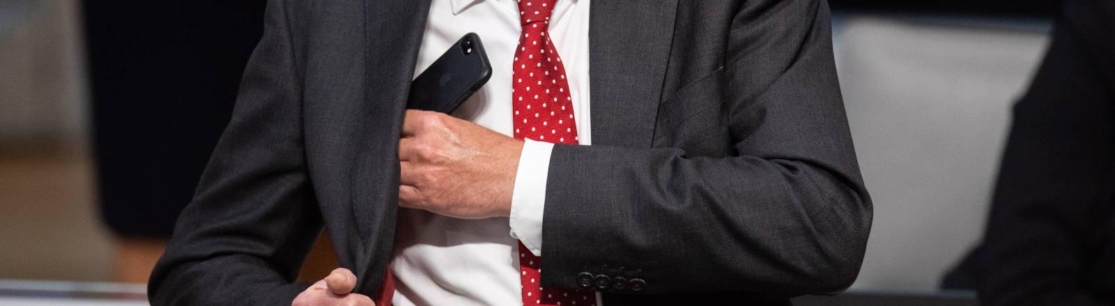 Ein Mann steckt ein Smartphone in seine Sakko-Tasche