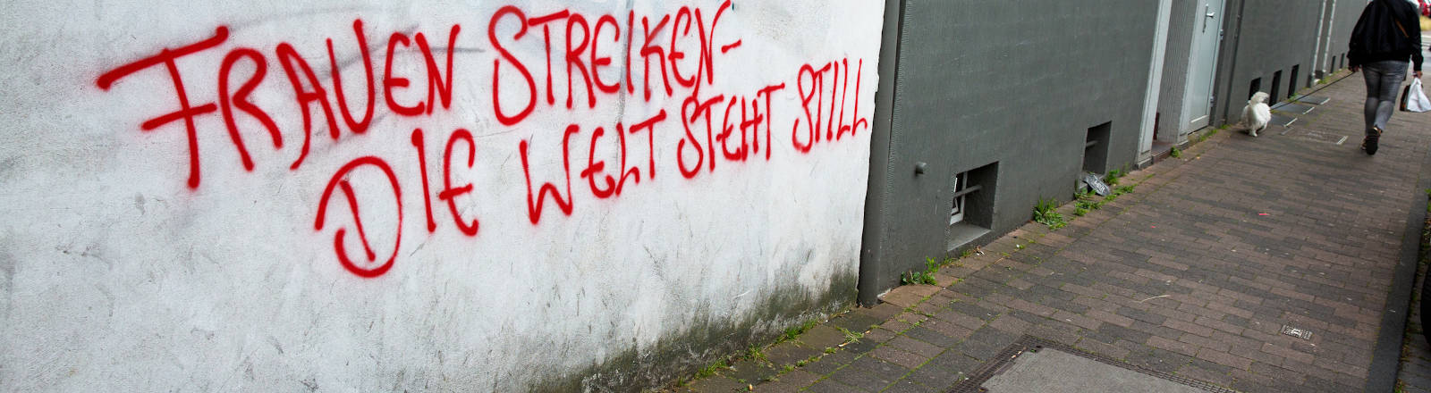 """Schriftzug auf Mauer """"Frauen streiken, die Welt steht still"""""""