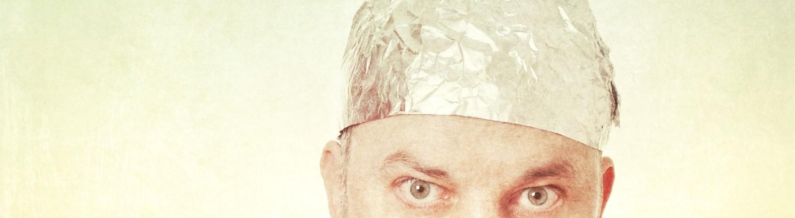 Ein Mann schaut grimmig. Er trägt einen Aluhut auf dem Kopf.
