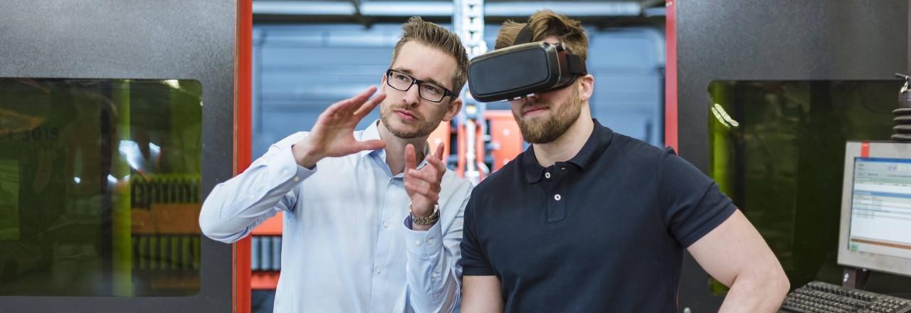 Zwei Männer stehen in der Montagehalle. Der eine trägt eine VR-Brille. Der zweite Mann erklärt ihm die Funktionen der Brille