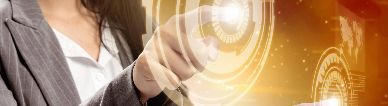 Eine Frau tippt mit den beiden Zeigefingern auf ein Display