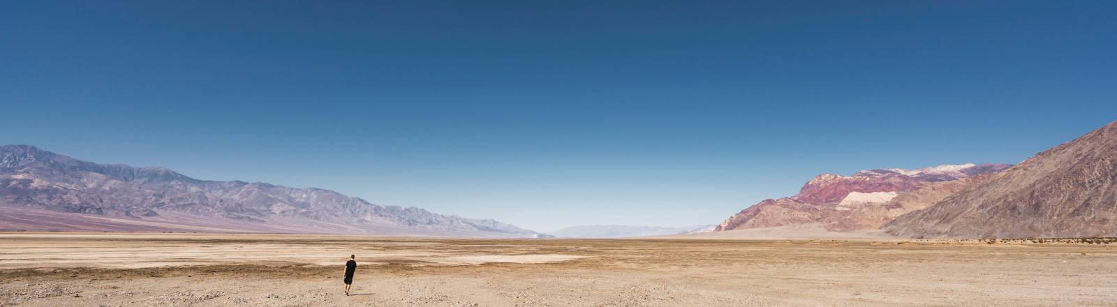 Ein Mann in der Wüste unter blauem Himmel