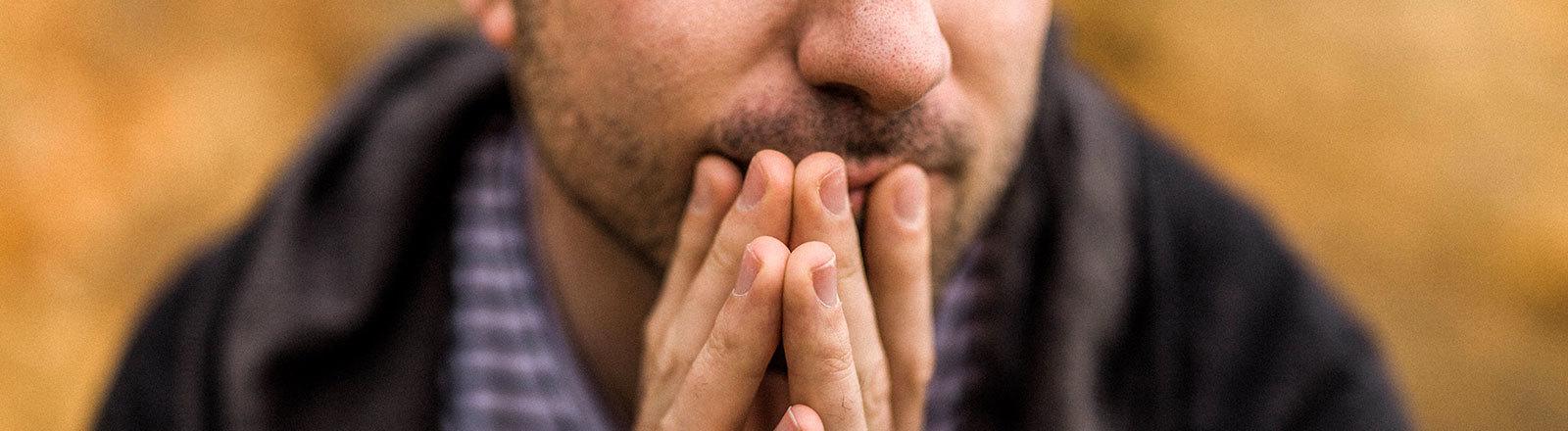 Ein Mann hält nachdenklich die Hände vor den Mund
