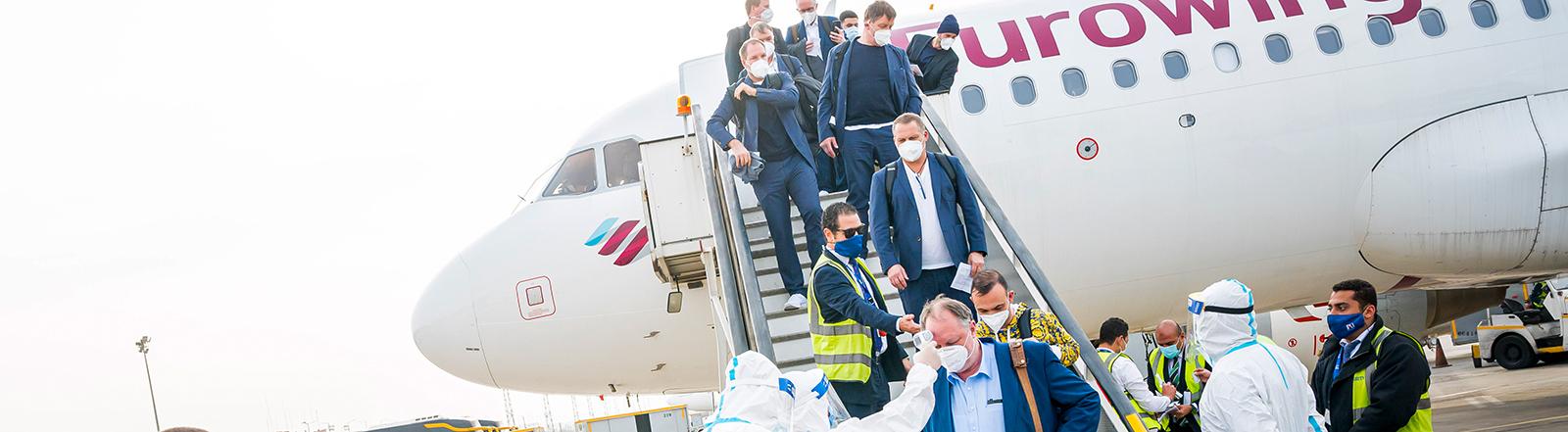 Aus dem Flugzeug steigt die deutsche Handball-Nationalmannschaft. Unten steht medizinisches Personal in Schutzanzügen; Foto: dpa (12.01.2021)